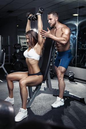 abdominal fitness: hermosa joven deportiva entrenamiento pareja sexy en el gimnasio