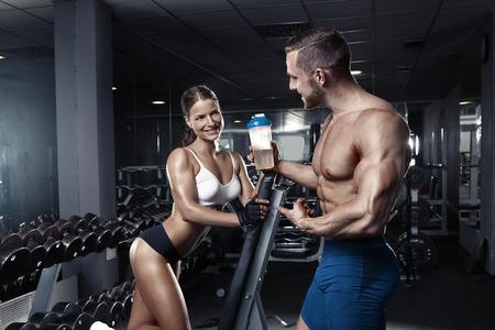 健身: 在健身房年輕漂亮的運動型的性感夫婦展示肌肉 版權商用圖片