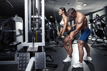 young male: beautiful young sporty sexy couple doing triceps workout in gym