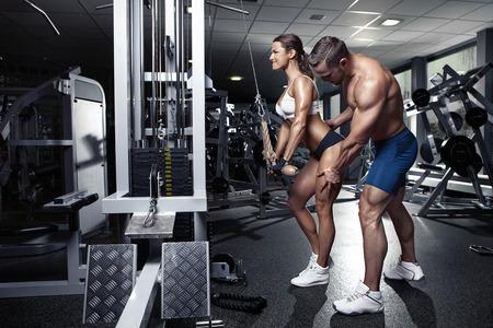 modelos hombres: hermosa joven deportiva atractiva pareja haciendo tríceps del entrenamiento en gimnasia