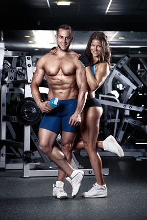 beautiful young sporty sexy couple showing muscle in gym