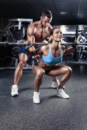 beautiful young sporty sexy couple doing squat workout in gym