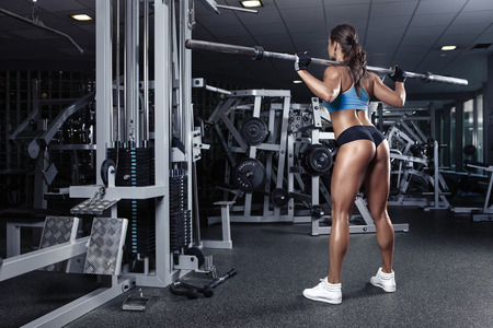 nude body: beautiful sporty sexy woman doing squat workout in gym