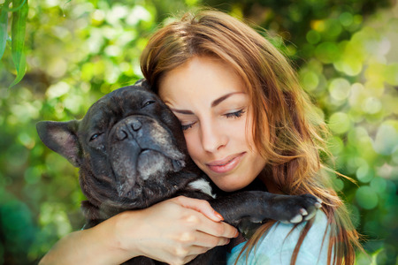 Happy woman with french bulldog on blurred nature background