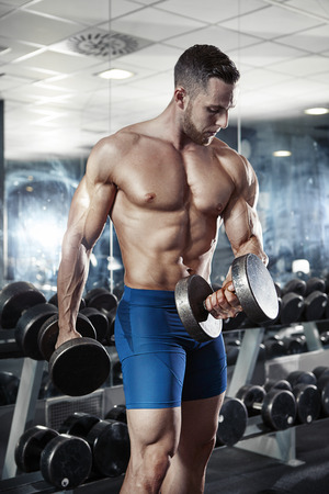 man arm: Muscular bodybuilder guy doing exercises with dumbbell in gym