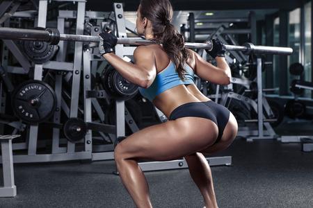 hermosa mujer sexy deportivo haciendo ejercicios en cuclillas en el gimnasio