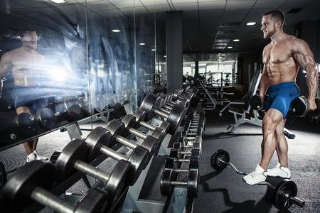 Gespierde bodybuilder man doet oefeningen met halters in de sportschool