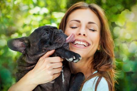 dog days: Mujer feliz con el bulldog franc�s sobre la naturaleza de fondo borrosa