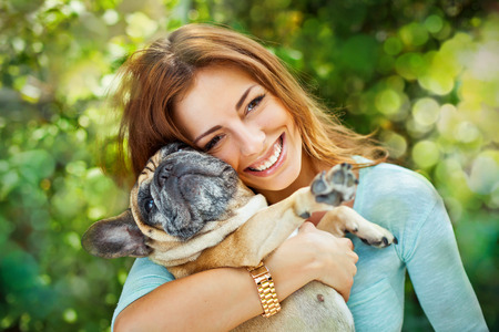 hand hold: Happy woman with french bulldog on blurred nature background