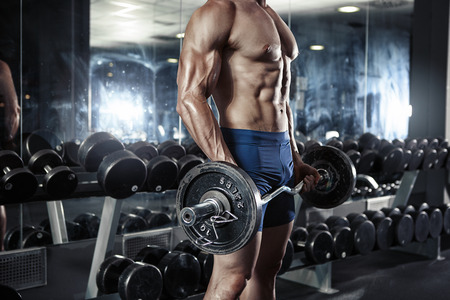 Muscular bodybuilder guy doing exercises with big dumbbell in gym Stock Photo