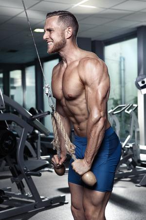 desnudo masculino: Chico culturista muscular que hace ejercicios de tríceps en el gimnasio