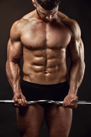 retouched: Muscular bodybuilder guy doing exercises with big dumbbell over black background