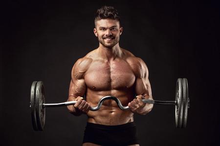 bodybuilder: Tipo culturista muscular haciendo ejercicios con pesa de gimnasia grande sobre fondo negro Foto de archivo