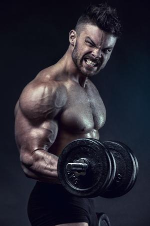 male body: Muscular bodybuilder guy doing exercises with dumbbells over black background