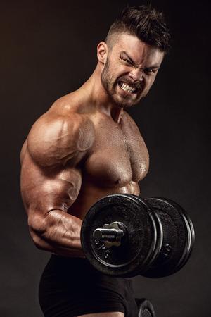 黒背景にダンベル体操をやって筋肉ボディービルダー男