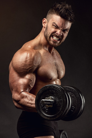 male bodybuilder: Muscular bodybuilder guy doing exercises with dumbbells over black background