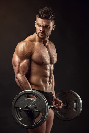 male athlete: Muscular bodybuilder guy doing exercises with big dumbbell over black background