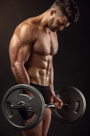 Muscular bodybuilder guy doing exercises with big dumbbell over black background