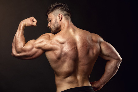 latissimus: Strong Athletic Man Fitness Model posing back muscles, triceps, latissimus over black background Stock Photo