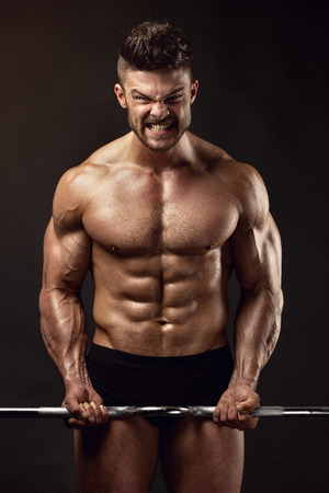 male body: Muscular bodybuilder guy doing exercises with big dumbbell over black background
