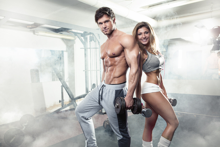 naked male body: beautiful young sporty sexy couple showing muscle and workout in gym Stock Photo