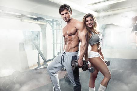 uomo nudo: giovane e bella sportiva sexy coppia che mostra muscoli e allenamento in palestra Archivio Fotografico