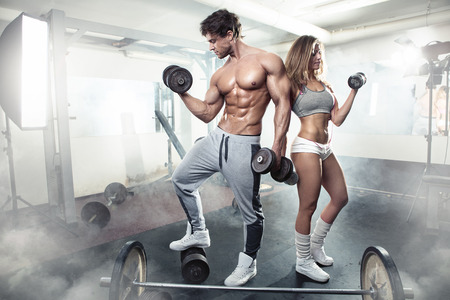 nude model: beautiful young sporty sexy couple showing muscle and workout in gym Stock Photo
