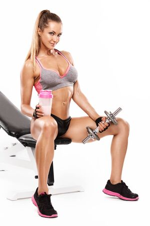 junge nackte m�dchen: Sch�ne reizvolle Frau auf einer Bank sitzen und dabei Training mit Hantel auf wei�em Hintergrund isoliert
