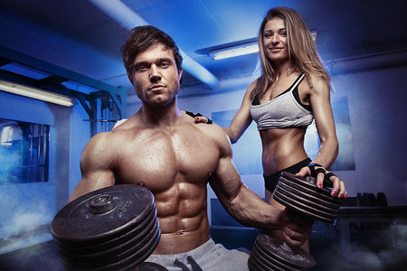 slim tummy: beautiful young sporty sexy couple showing muscle and workout in gym Stock Photo