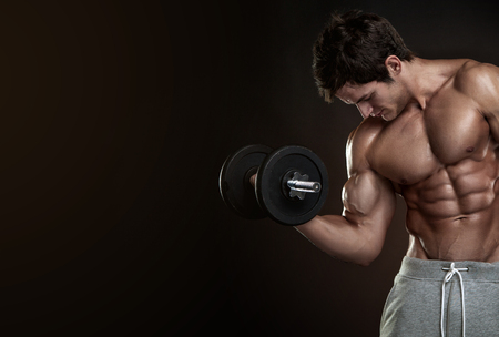 Muscular bodybuilder guy doing exercises with dumbbells over black background with copyspace