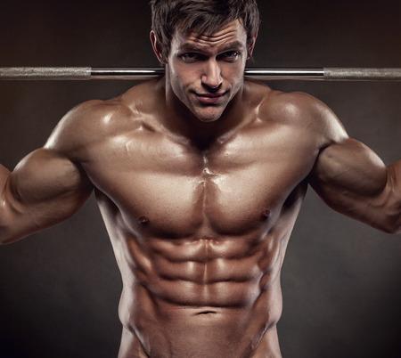 sixpack: Muscular bodybuilder guy doing exercises with dumbbells over black background