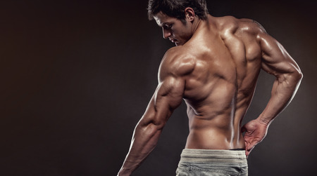nude pose: Strong Athletic Man Fitness Model posing back muscles, triceps, latissimus with copyspace Stock Photo