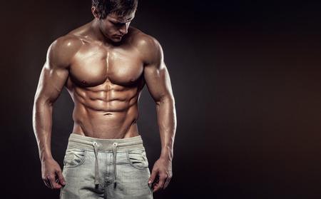 homme nu: Forte Athletic Man Fitness Model Torso montrant six pack abs. isolé sur fond noir avec copyspace