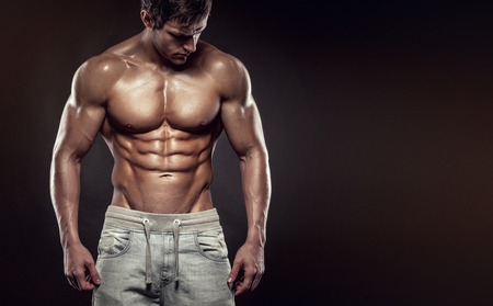 modelo desnuda: Fuerte Hombre Atl�tico modelo de la aptitud del torso mostrando abdominales perfectos. aislado en el fondo negro con copyspace