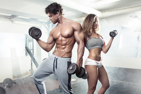nude abs: beautiful young sporty sexy couple showing muscle and workout in gym Stock Photo