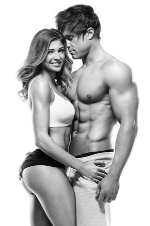 sexo pareja joven: pareja sexy, hombre musculoso sosteniendo una hermosa mujer aislada en un fondo blanco