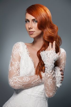 hair style: portrait of beautiful woman in wedding dress isolated over white background