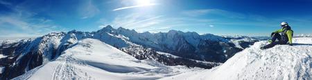 skiër zitten op de top van een berg en ontspannen, mooie achtergrond blauwe hemel