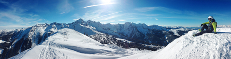skier sitting on top of a mountain and relaxing, beautiful background blue sky Standard-Bild