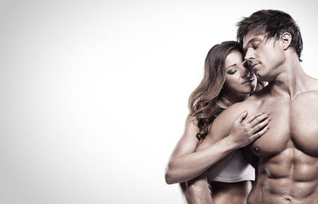 romantic sex: sexy couple, muscular man holding a beautiful woman isolated on a white background