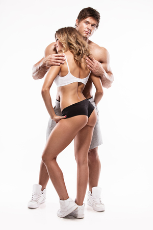 naked male body: sexy couple, muscular man holding a beautiful woman isolated on a white background