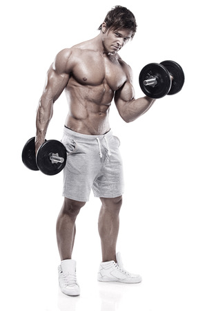 male athlete: Muscular bodybuilder guy doing exercises with dumbbells over black background