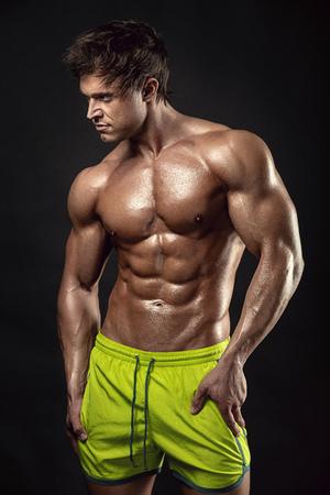 desnudo masculino: Fuerte Hombre Atlético modelo de la aptitud del torso mostrando grandes músculos sobre fondo negro Foto de archivo