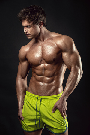 Strong Athletic Man Fitness Model Torso showing big muscles over black background Standard-Bild