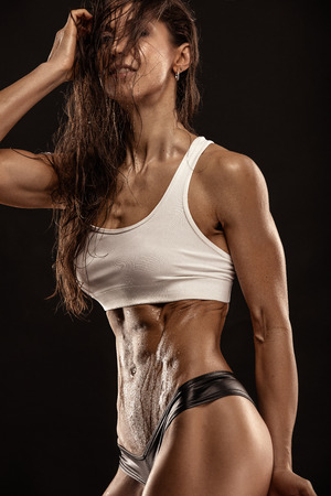 nude abs: Nice sexy fitness woman showing abdominal muscles, retouched isolated over black background Stock Photo