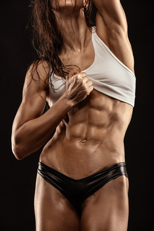 black breast: Nice sexy fitness woman showing abdominal muscles, retouched isolated over black background Stock Photo