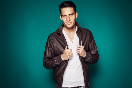 retouched: Cool young sexy fashion man standing over color background (retouched)