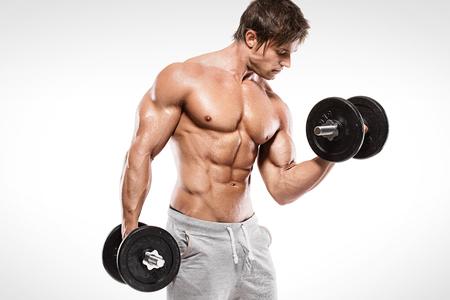 Muscular bodybuilder guy doing exercises with dumbbells over white background