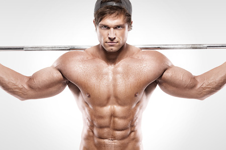over white: Muscular bodybuilder guy doing exercises with big dumbbell over white background