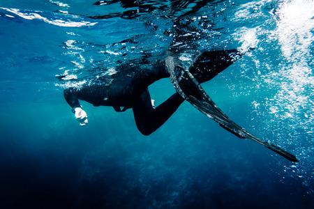 Freediver in wetsuit neopreen zwemmen in de zee